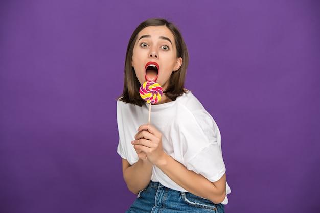 다채로운 사탕을 가진 젊은 여자