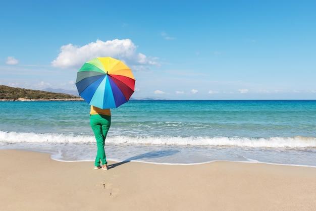 Молодая женщина с красочным зонтиком на пляже
