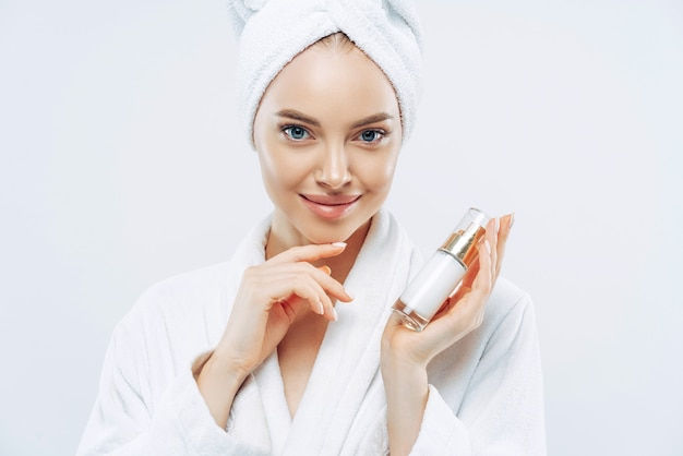 Young woman with confident expression, healthy clean smooth skin, well groomed complexion, holds bottle of lotion or gel, touches jawline, dressed in bath robe.