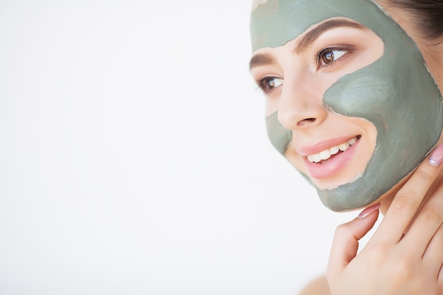 Young woman with cosmetic clay mask
