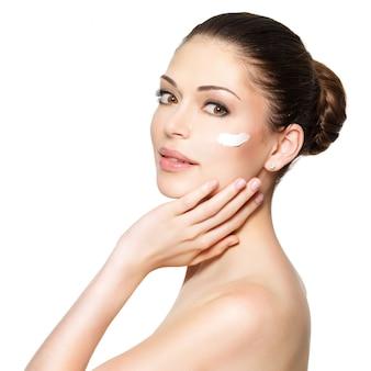 Giovane donna con crema cosmetica su un viso fresco e pulito. concetto di cura della pelle