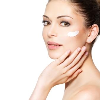 きれいな新鮮な顔に化粧クリームを持つ若い女性。スキンケアのコンセプト