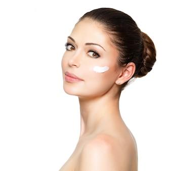きれいな新鮮な顔に化粧クリームを持つ若い女性