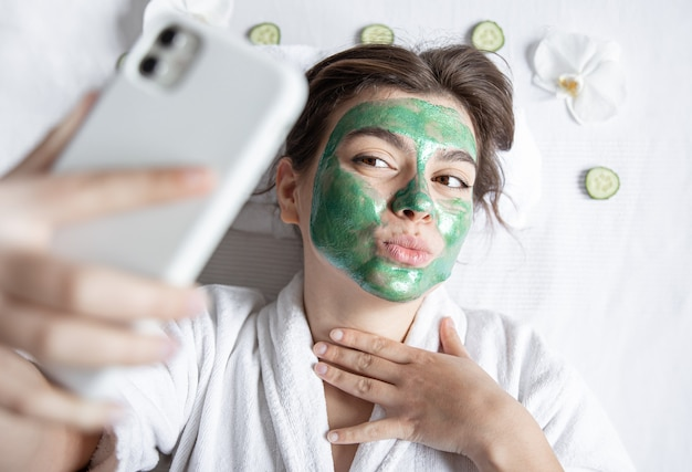 Young woman with a cosmetic mask on her face makes a selfie on a smartphone.
