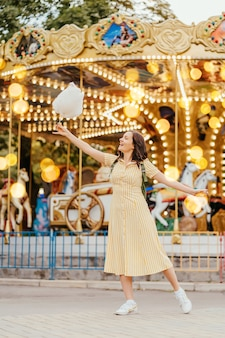 Молодая женщина с сахарной ватой перед каруселью с ночным освещением в парке развлечений.