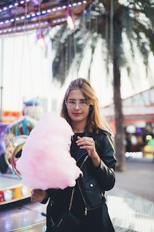 Giovane donna con zucchero filato alla festa