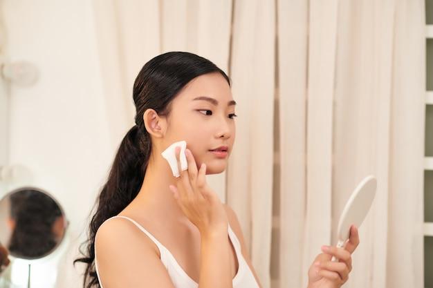 鏡の近くで顔を拭く綿パッドを持つ若い女性
