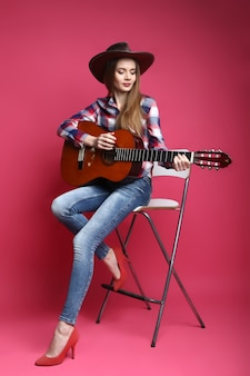 Young woman with cowboy hat and guitar on a pink background