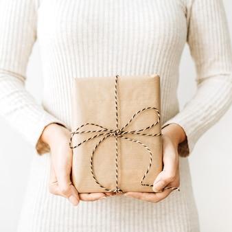 흰색 표면에 공예 선물 상자를 가진 젊은 여자.