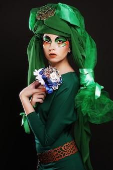 창의적인 메이크업 보석 꽃다발을 들고 젊은 여자