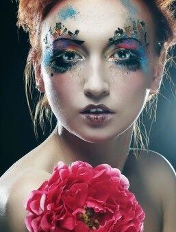 Молодая женщина с творческим макияжем держит большой розовый цветок