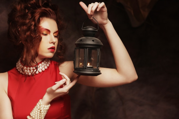 Young woman with creative make-up holding a candle