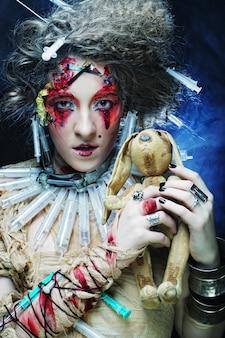 小さなウサギを保持している創造的なメイクアップを持つ若い女性。