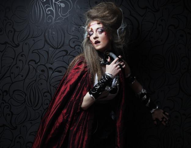 빨간 비옷에 창의적인 메이크업을 하는 젊은 여자. 할로윈 테마입니다. 좀비 테마입니다.