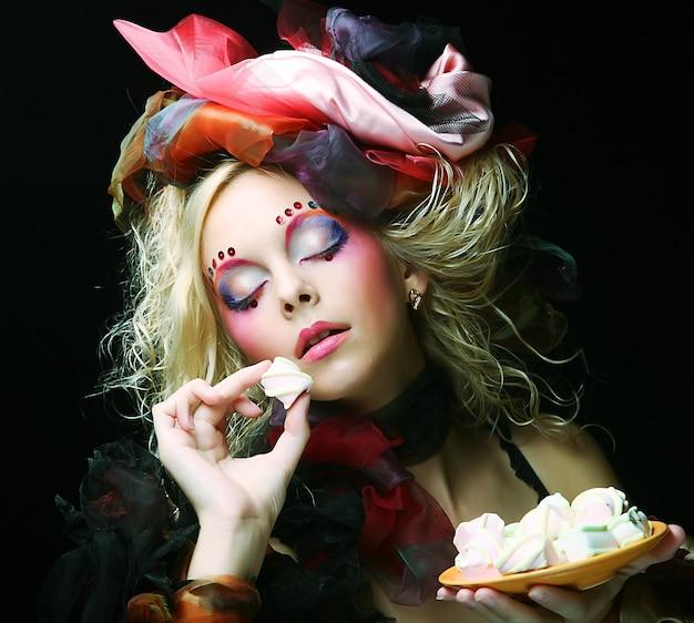 ケーキと人形のスタイルで創造的なメイクアップの若い女性。