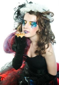 Молодая женщина с творческим макияжем в стиле куклы с тортом.