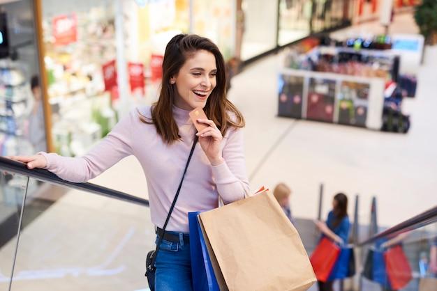 クレジットカードと完全な買い物袋を持つ若い女性