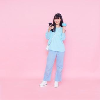 ピンクの壁にクレジットカードとスマートフォンを持つ若い女性。オンラインショッピング