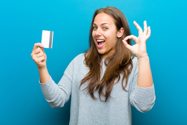 Young woman with a credit card   blue wall