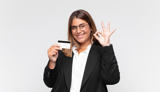 Young woman with a credit card feeling happy, relaxed and satisfied, showing approval with okay gesture, smiling