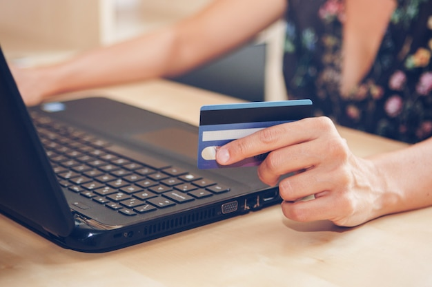 Young woman with a credit card is shopping online in the office