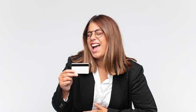 Young woman with a credit card laughing out loud at some hilarious joke, feeling happy and cheerful