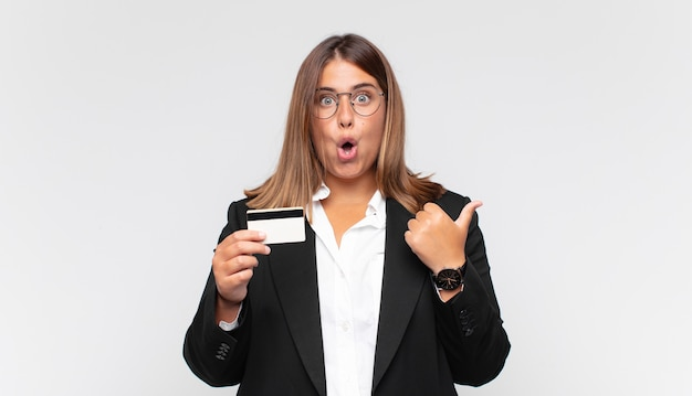 Young woman with a credit card looking astonished in disbelief, pointing at object on the side and saying wow, unbelievable