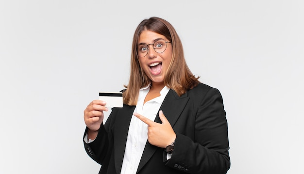 Young woman with a credit card looking excited and surprised pointing to the side and upwards to copy space