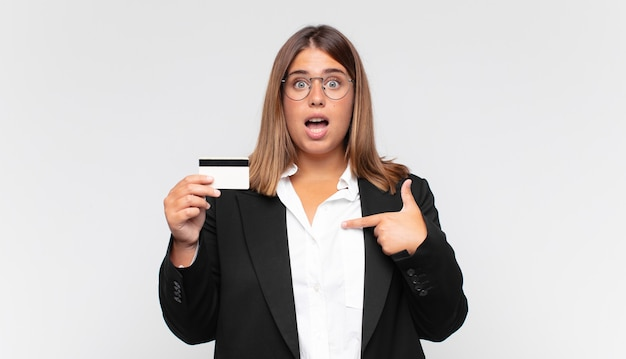 Young woman with a credit card looking shocked and surprised with mouth wide open, pointing to self