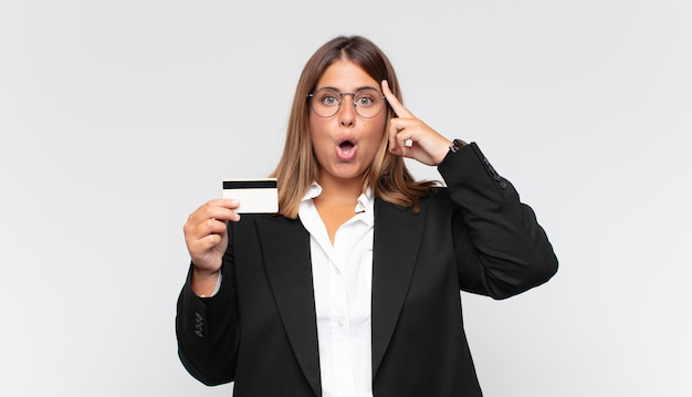 Young woman with a credit card looking surprised, open-mouthed, shocked, realizing a new thought, idea or concept
