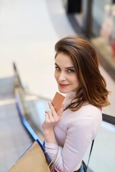 Giovane donna con carta di credito e borse della spesa