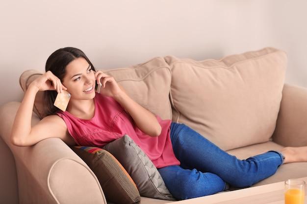 自宅で携帯電話で話しているクレジットカードを持つ若い女性。オンラインショッピング