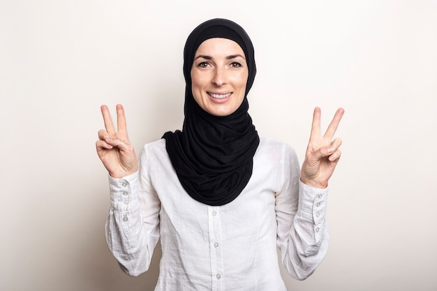 Young woman with crossed arms dressed in a white shirt and hijab shows a welcome gesture all is well