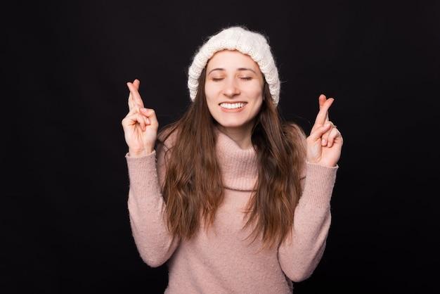 교차 손가락과 눈을 감은 젊은 여자는 무언가를 희망하거나 희망합니다.