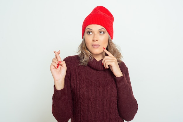 Young woman with crossed fingers looking aside
