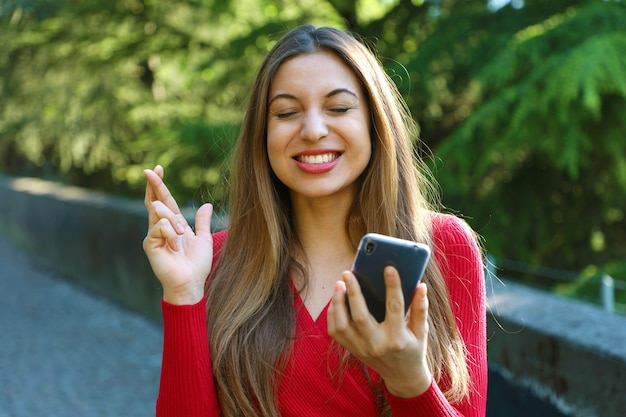 Young woman with crossing fingers and smart phone wishing the best outside