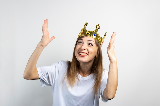 Young woman with a crown on her head emotionally rejoices and celebrates on a light background