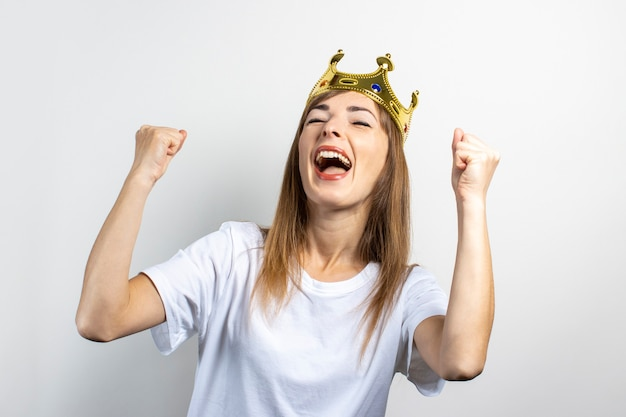 Young woman with a crown on her head emotionally rejoices and celebrates