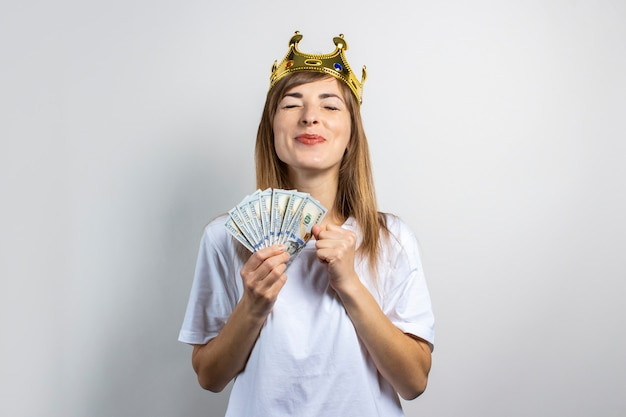 Young woman with a crown on her head holds a stack of money and celebrates very joyfully on a light background