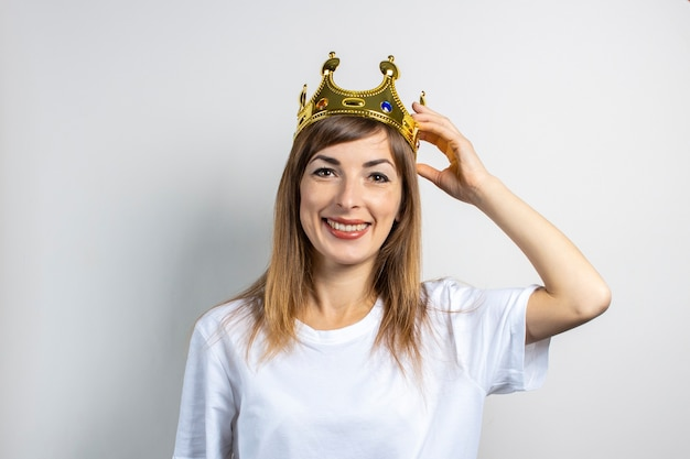 Young woman with a crown on her head on a light background