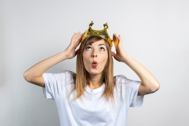 Young woman with a crown on her head and a surprised face.