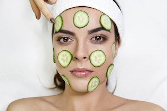 Young woman with cucumber mask lies on white table in spa saloon