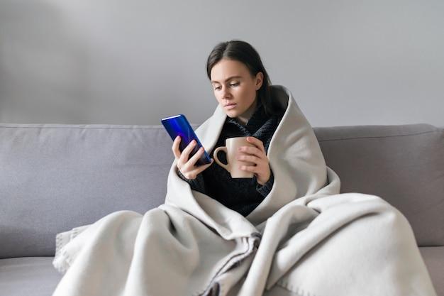 Молодая женщина с чашкой и смартфоном
