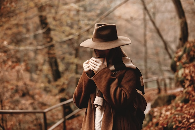 Young woman with cup of coffee in an autumn season park