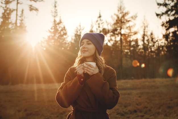 Young woman with cup of coffee stay near wood in sunset time