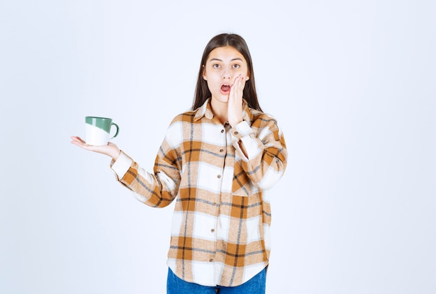 Young woman with cup of coffee surprised about something.