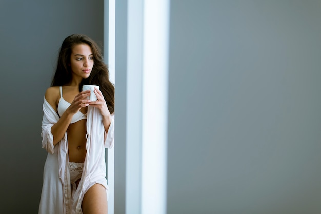 Young woman with cup of coffee or tea in neglige standing by the window