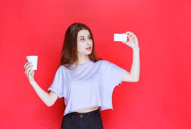 Young woman with a cup of drink presenting her business card.