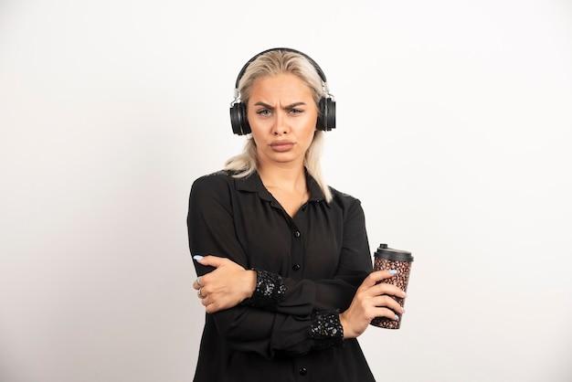 赤い背景の上のヘッドフォンでカップを持つ若い女性。高品質の写真