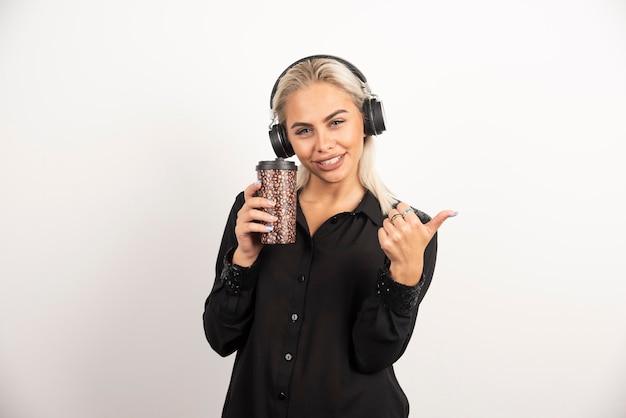 빨간 벽에 엄지 손가락을 보여주는 헤드폰에 컵을 가진 젊은 여자.